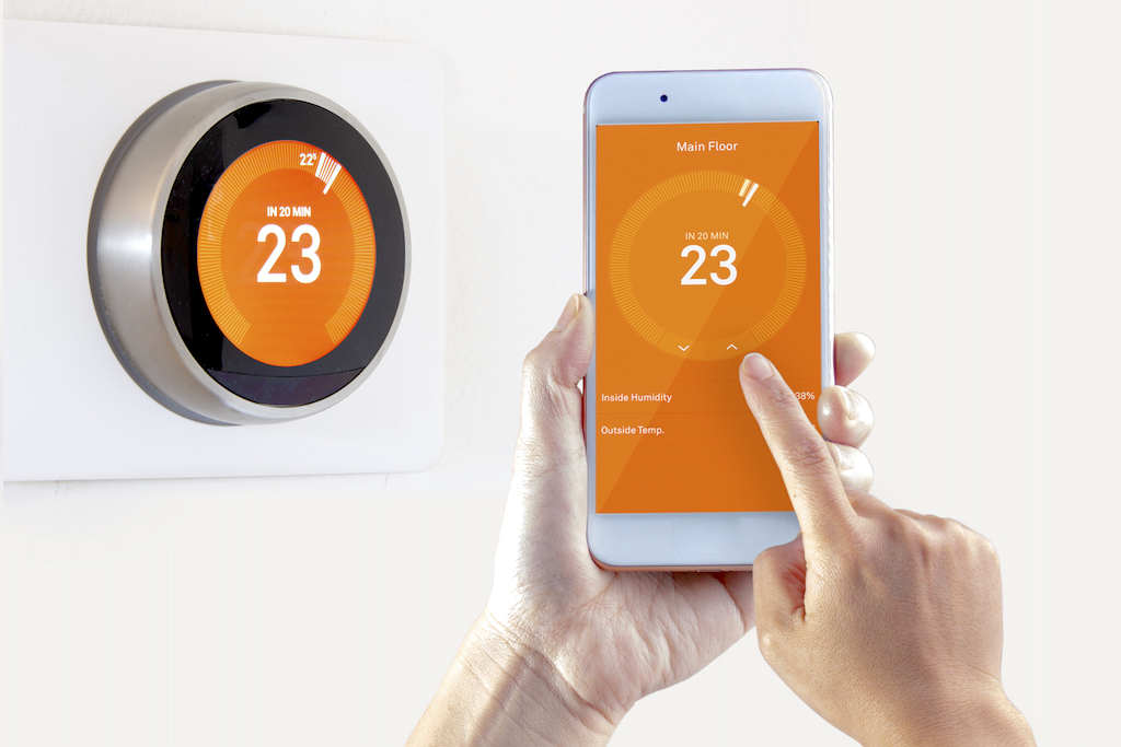 Smart Thermostat and a person setting up the temperature with a smart device on a white background